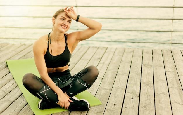 Zmęczona muskularna kobieta w odzieży sportowej odpoczywa siedząc na macie na tarasie plaży.