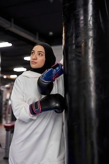 Zmęczona muzułmańska sportsmenka stojąca przy worku treningowym po ciężkim treningu, ubrana w rękawice bokserskie i sportowy biały hidżab, patrzy w bok, wyczerpana