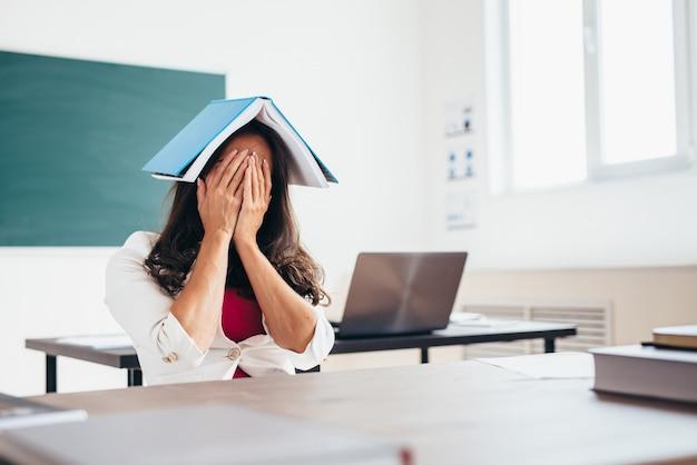 Zmęczona nauczycielka siedzi przy stole z książką na głowie.