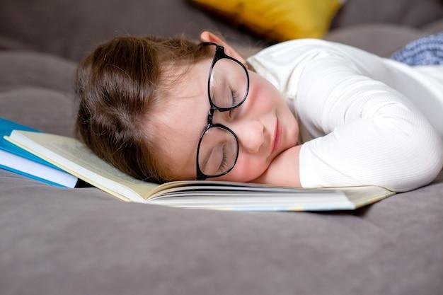 Zmęczona nauką i czytaniem śliczna mała dziewczynka w okularach śpi na łóżku na otwartej księdze