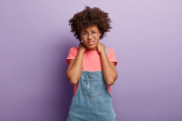 Zmęczona, niezadowolona, radosna kobieta ma afro włosy, trzyma obie ręce na szyi, uśmiecha się z bólu, jest zmęczona pracą przy komputerze