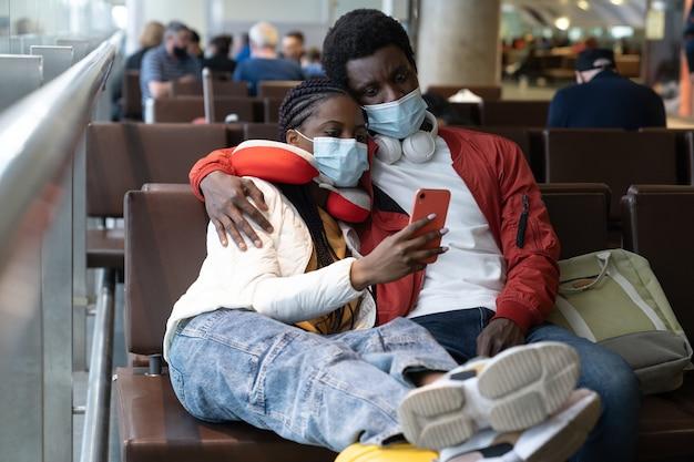 Zmęczona para turystów w maskach na lotnisku czeka na opóźniony lot, odwołany z powodu kryminalnej blokady
