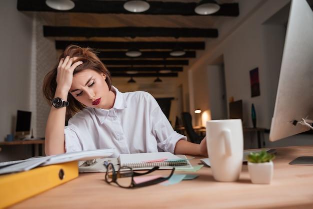 Zmęczona piękna kobieta w biurze.
