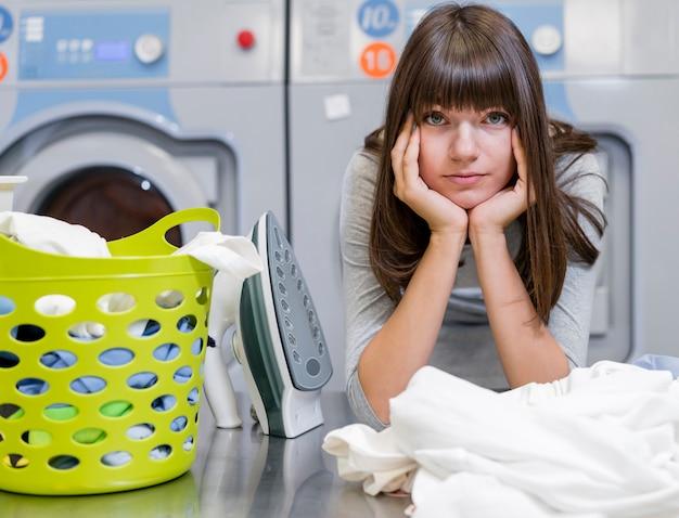 Zmęczona piękna kobieta w pralni pokoju