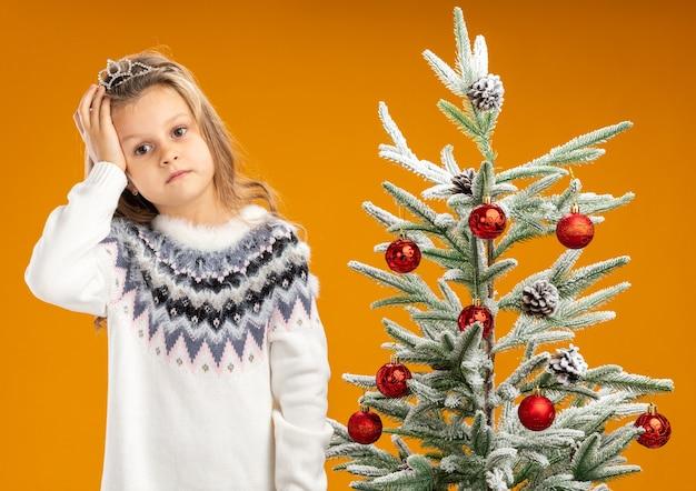 Zmęczona przechylana głowa mała dziewczynka stojąca w pobliżu choinki w diademie z girlandą na szyi kładąca dłoń na głowie na białym tle na pomarańczowym tle