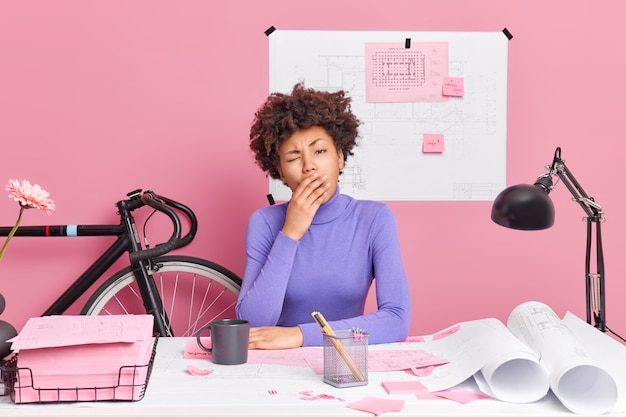 Zmęczona, przepracowana, ciemnoskóra młoda kobieta ziewa i ma zaspane pozy przy biurku, ma termin na przygotowanie się do pracy nad projektem, czuje się wyczerpana ukończeniem pracy