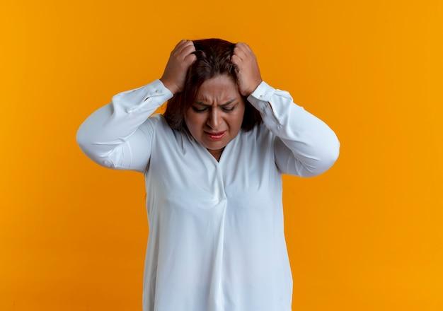 Zmęczona przypadkowa kaukaski kobieta w średnim wieku złapała głowę odizolowaną na żółtej ścianie