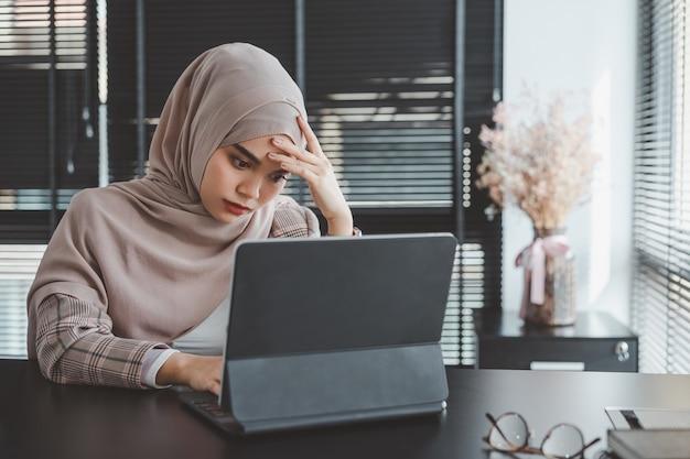 Zmęczona sfrustrowana młoda muzułmańska biznesowa kobieta brązowy hidżab zestresowany trzymając głowę rękami, koncepcja niepowodzenia problemu biznesowego