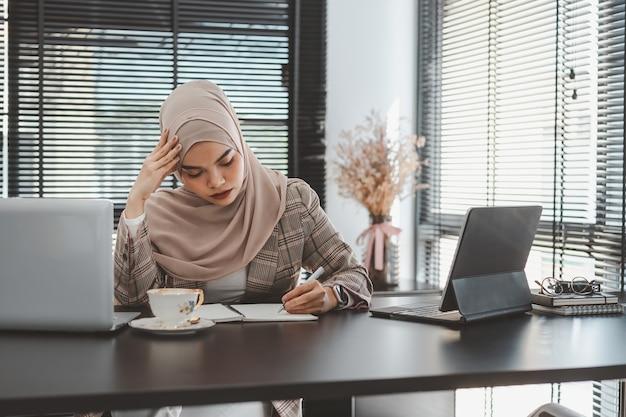 Zmęczona sfrustrowana młoda muzułmańska biznesowa kobieta brązowy hidżab zestresowany trzymając głowę rękami
