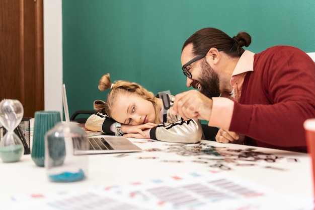 Zmęczona śliczna jasnowłosa dziewczyna z bransoletkami na dłoni czuje się zmęczona podczas myślenia nad literami
