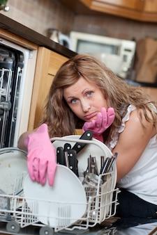 Zmęczona śliczna kobieta segreguje zmywarka do naczyń