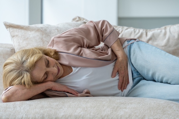 Zmęczona stara kobieta w zwykłych ubraniach ma ból brzucha leżąc na kanapie w domu