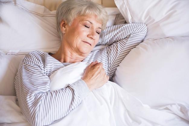 Zmęczona starsza kobieta śpi w łóżku