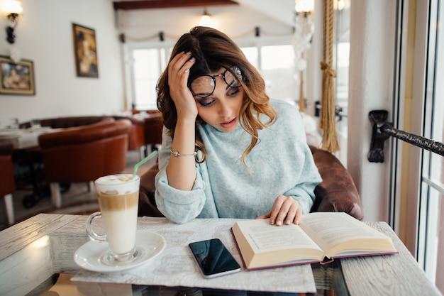 Zmęczona studencka dziewczyna czyta literaturę naukową w kawiarni
