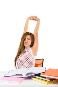 Zmęczona studentka dziewczyna z książkami na białym tle na białej ścianie