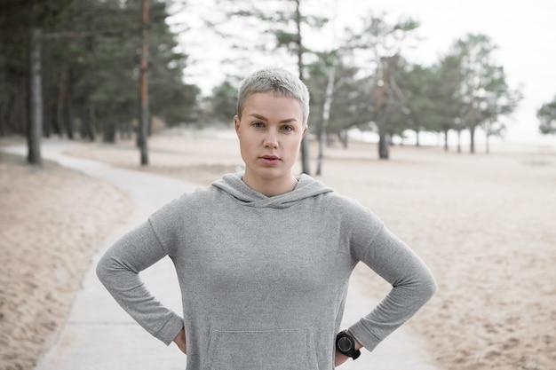 Zmęczona szczupła dziewczyna w bluzie z kapturem pozuje na zewnątrz, trzymając ręce na jej talii i patrząc w kamerę, odpoczywając podczas treningu cardio. koncepcja ludzie, styl życia, aktywność, zdrowie i fitness