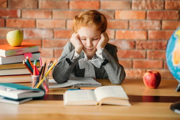Zmęczona uczennica odrabia lekcje przy stole z podręcznikami, jabłkami i kulą ziemską.