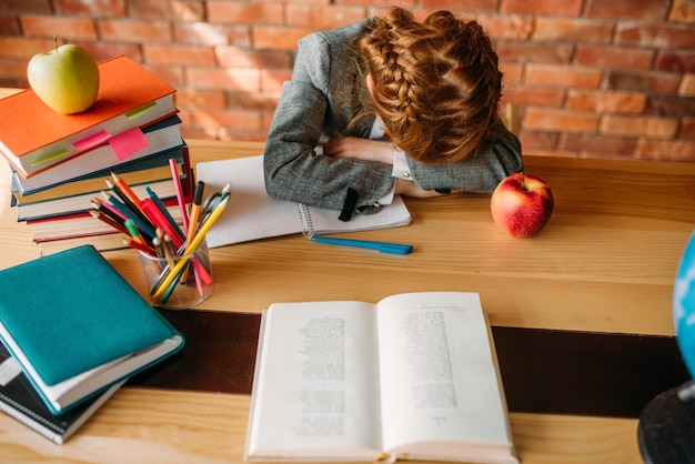 Zmęczona uczennica śpi przy stole z otwartym zeszytem.