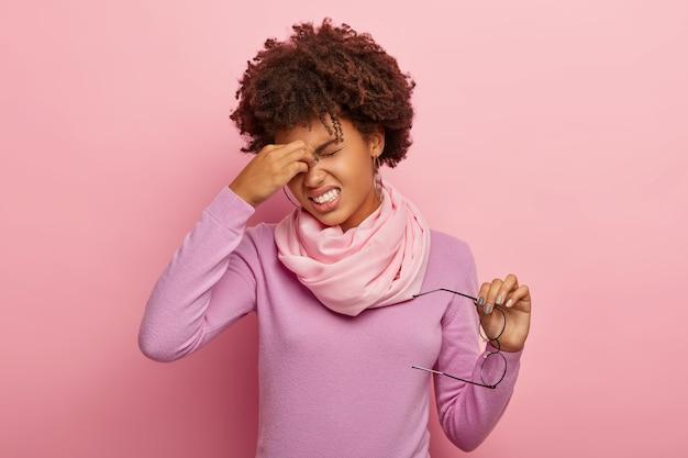 Zmęczona wyczerpana kobieta masuje oczy, odczuwa dyskomfort z powodu bólu po długim czytaniu, potrzebuje kropli do oczu