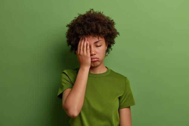Zmęczona wyczerpana kobieta robi dłoń na twarzy, ma problemy ze zdrowiem, senną niezadowoloną minę, wzdycha ze zmęczenia, nosi niezobowiązującą zieloną koszulkę, pozuje w domu. uczucie zmęczenia i przepracowania