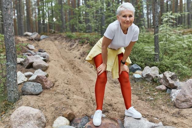 Zmęczona, wyczerpana kobieta w średnim wieku w sportowej odzieży i butach do biegania, odpoczywająca po intensywnym treningu cardio