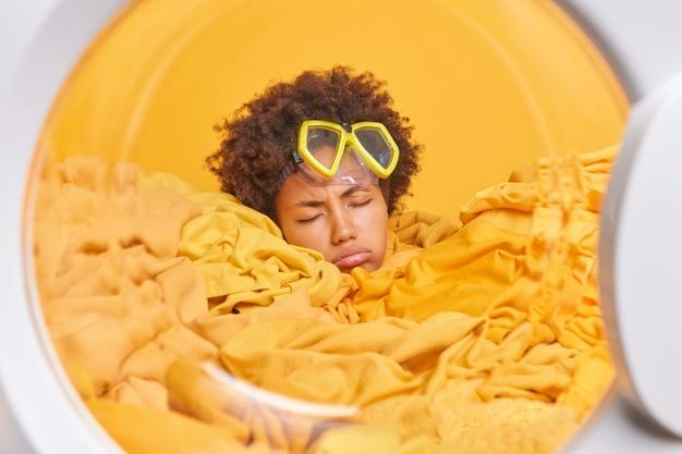 Zmęczona, wyczerpana młoda kobieta gospodyni ma zaspany wyraz twarzy zajęty praniem w domu, nosi maskę do nurkowania w otoczeniu brudnych ubrań w pralce
