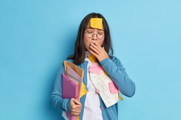 Zmęczona wyczerpana studentka ziewa i ma senną minę przepracowana długie godziny zakrywa usta ręką trzyma teczki z karteczkami próbuje nauczyć się całego materiału do egzaminu.