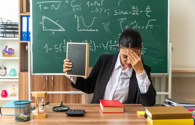 Zmęczona z opuszczoną głową młoda nauczycielka siedzi przy stole z szkolnymi narzędziami, trzymając w klasie mini tablicę
