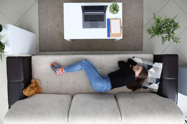 Zmęczona z pracy dziewczyna śpi w domu na kanapie