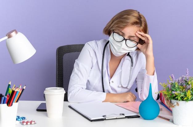 Zmęczona z zamkniętymi oczami młoda lekarka nosząca szatę medyczną ze stetoskopem i okularami z maską medyczną siedzi przy stole z narzędziami medycznymi na białym tle na niebieskim tle
