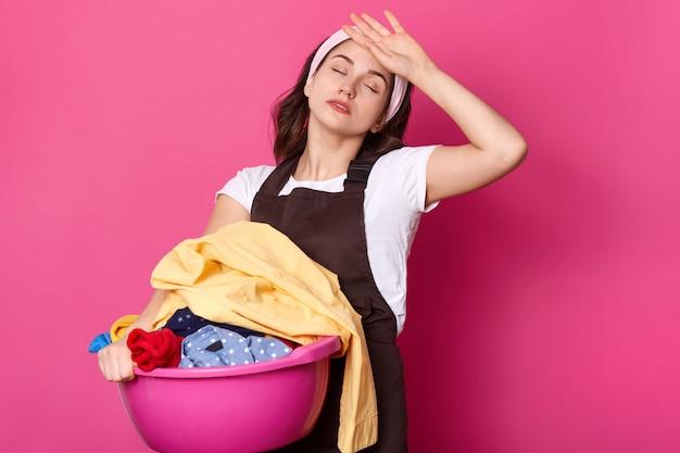 Zmęczona zajęta europejka trzyma umywalkę z brudnymi ubraniami