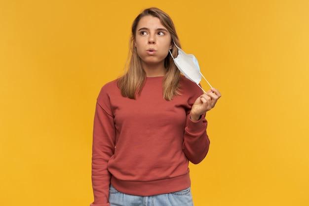 Zmęczona zamyślona młoda kobieta zdejmująca maseczkę na twarz z zimną grypą i biorąca oddech na żółtej ścianie