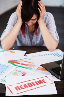 Zmęczona zaniepokojona pracownica z bólem głowy. zestresowana kobieta w biurze, trzymając głowę w ręce i myśląc o terminie