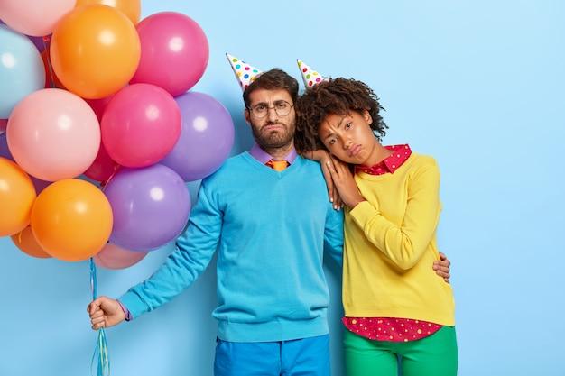 Zmęczona zdenerwowana różnorodna kobieta i mężczyzna noszą urodzinowe czapki