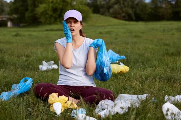 Zmęczona zdziwiona kobieta podnosi śmieci na zielonej łące