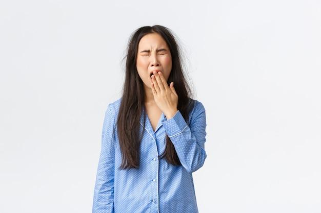 Zmęczona ziewająca dziewczyna w niebieskiej piżamie, po przebudzeniu ziewająca zaspana z niechlujną fryzurą, zakrywająca otwarte usta dłonią, stojąca w dżinsach po ciężkiej nocy, białe tło.