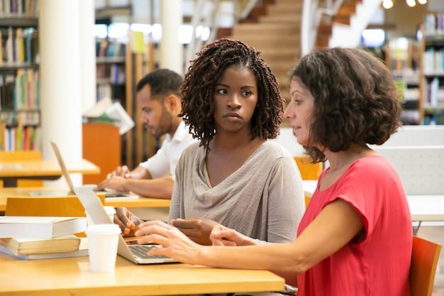 Zmęczone kobiety używa laptop przy biblioteką