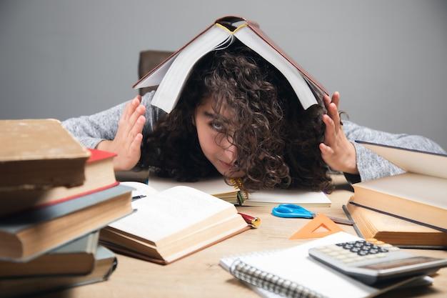 Zmęczone książki studenckie dziewczyna w głowie.