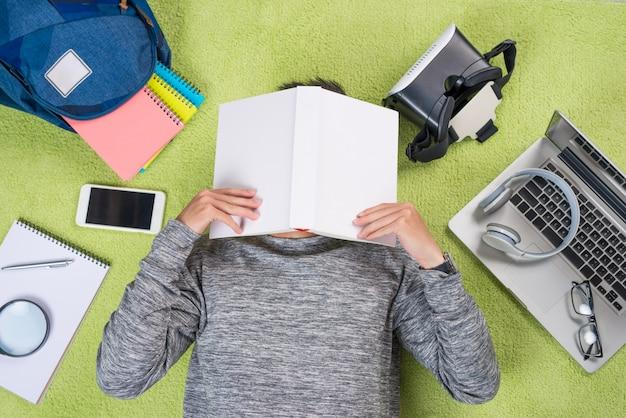 Zmęczony azjatycki młody człowiek z książką na twarzy leżącego na podłodze.