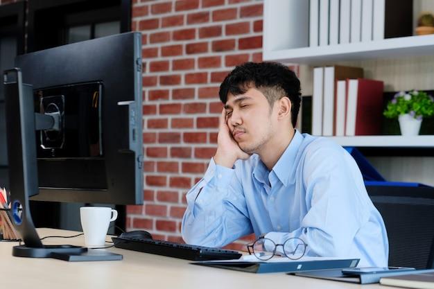 Zmęczony azjatykci mężczyzna dosypianie przy biurowym biurkiem