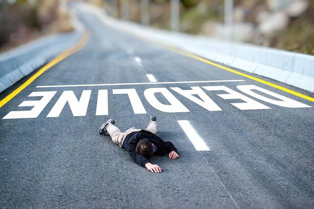 Zmęczony bezsilny mężczyzna w czarnej kurtce i szarych spodniach upadł na drogę pokonuje termin napisany tytuł