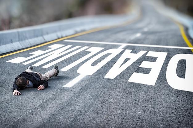 Zmęczony bezsilny mężczyzna w czarnej kurtce upadły na drogę pokonuje termin napisany na asfalcie