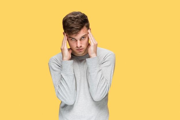 Zmęczony biznesmen lub poważny młody człowiek na żółtej ścianie z emocjami bólu głowy