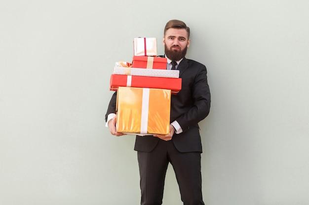 Zmęczony biznesmen posiadający bardzo ciężkie pudełka. studio strzał, szare tło
