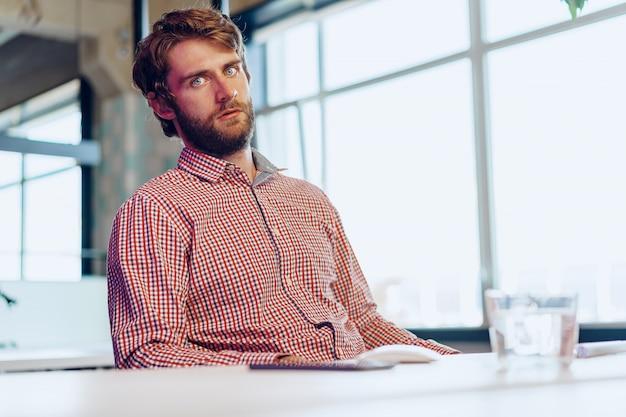 Zmęczony biznesmen pracuje na jego komputerze w otwartej przestrzeni biurze. koniec dnia roboczego