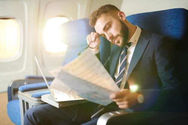 Zmęczony biznesmen pracuje w samolocie