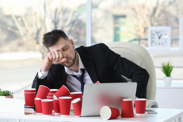 Zmęczony biznesmen siedzi w miejscu pracy ze stertą papierowych kubków do kawy w biurze
