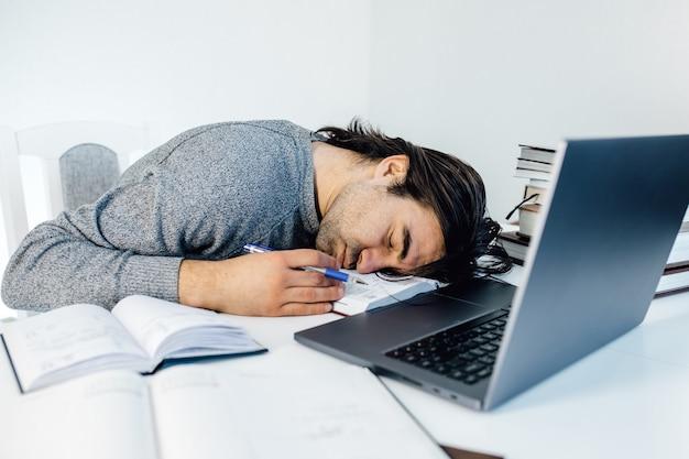Zmęczony biznesmen śpi podczas obliczania wydatków przy biurku w biurze. młody pracownik płci męskiej rasy kaukaskiej ucina sobie drzemkę w biurze na stole z tabletem i laptopem..