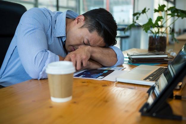 Zmęczony biznesmen śpi przy biurku