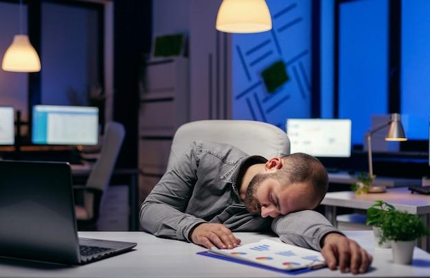 Zmęczony biznesmen śpi w swoim miejscu pracy na biurku. pracoholik zasypia z powodu pracy do późnych godzin nocnych sam w biurze przy ważnym dla firmy projekcie.